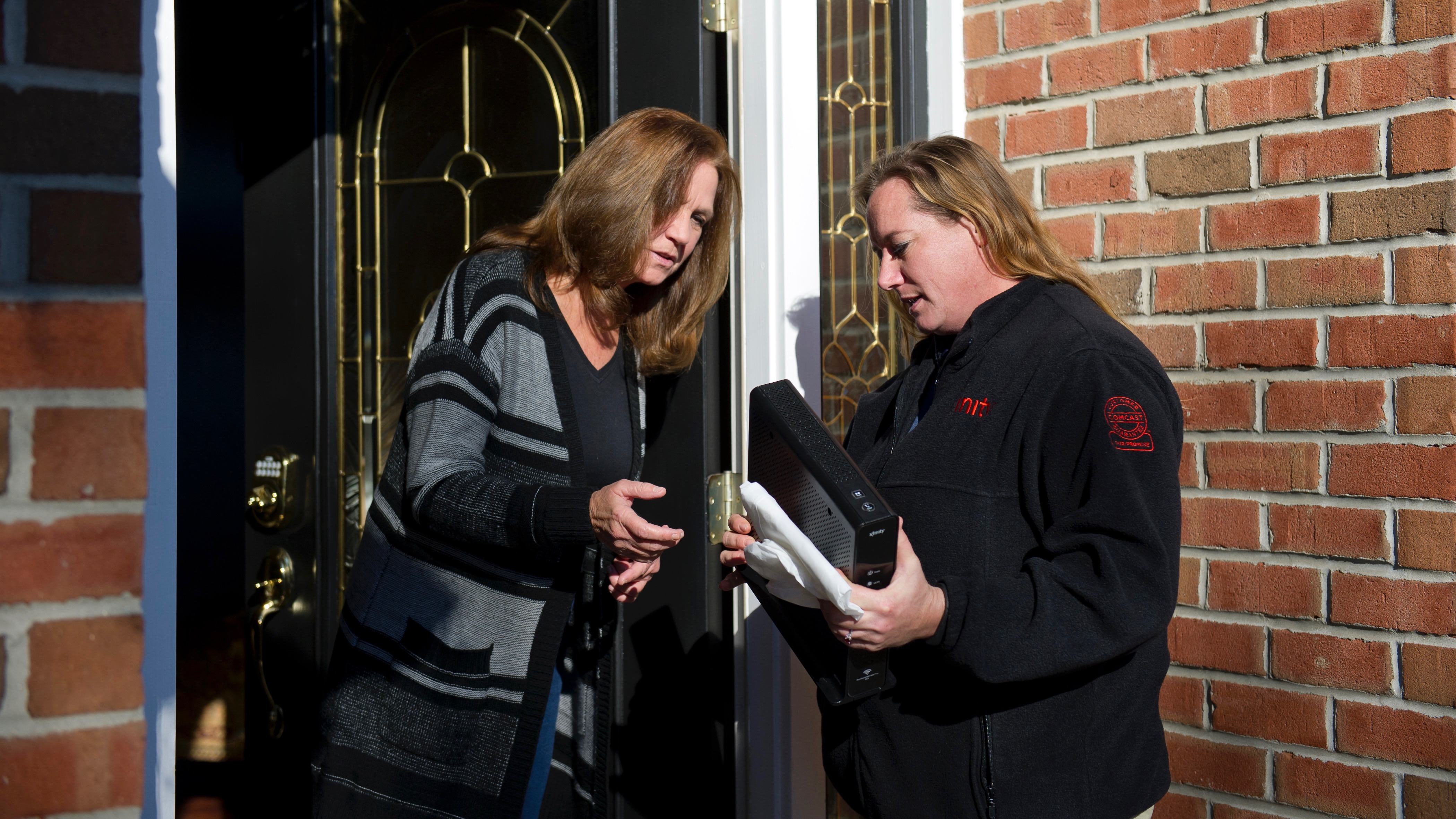An Xfinity technician speaks with a customer in their doorway.