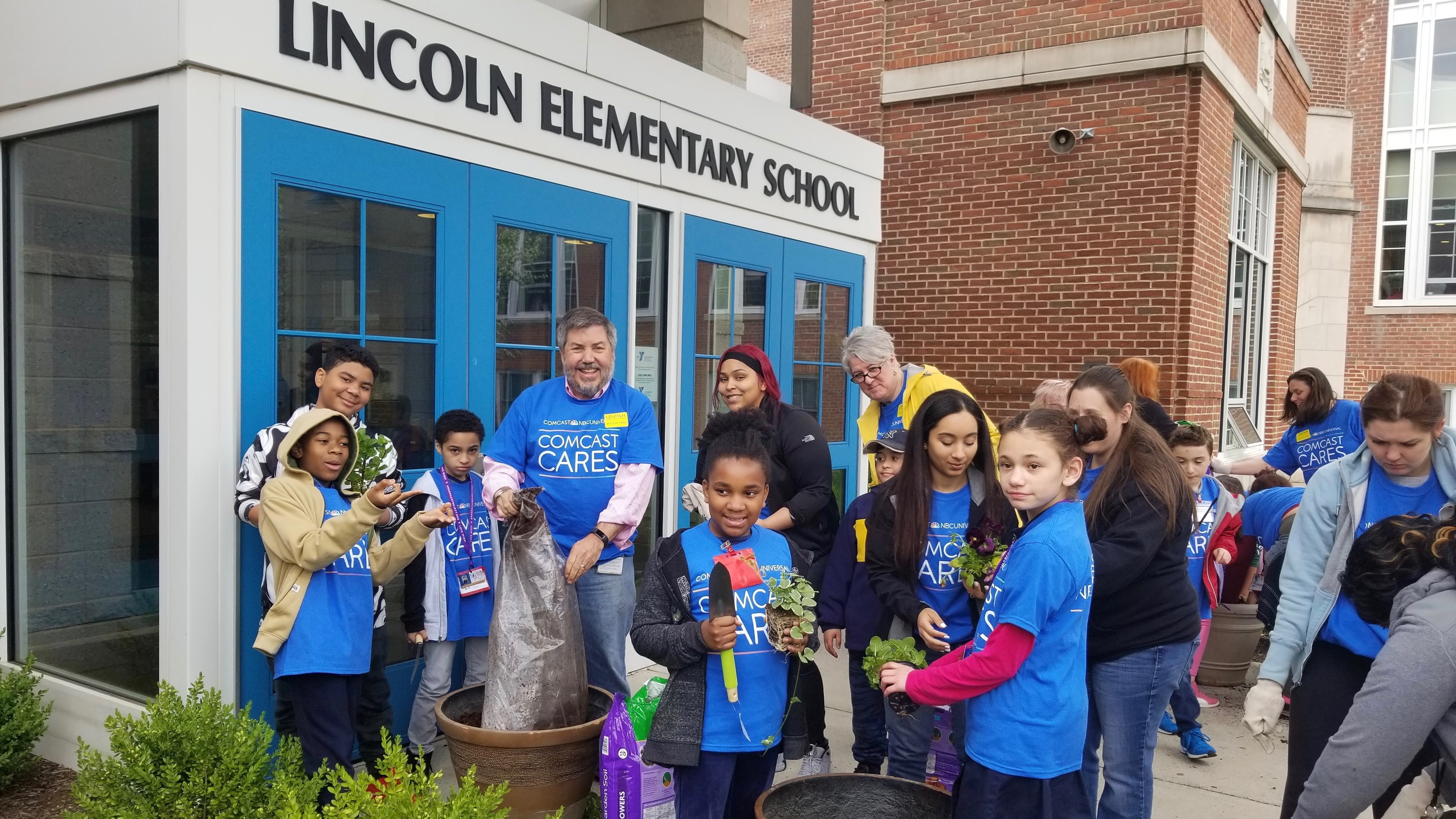 Young Comcast Cares Day volunteers stand outside of Lincoln Elementary School.