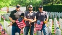 Three Xfinity employees hold American flags as they stand in a graveyard.