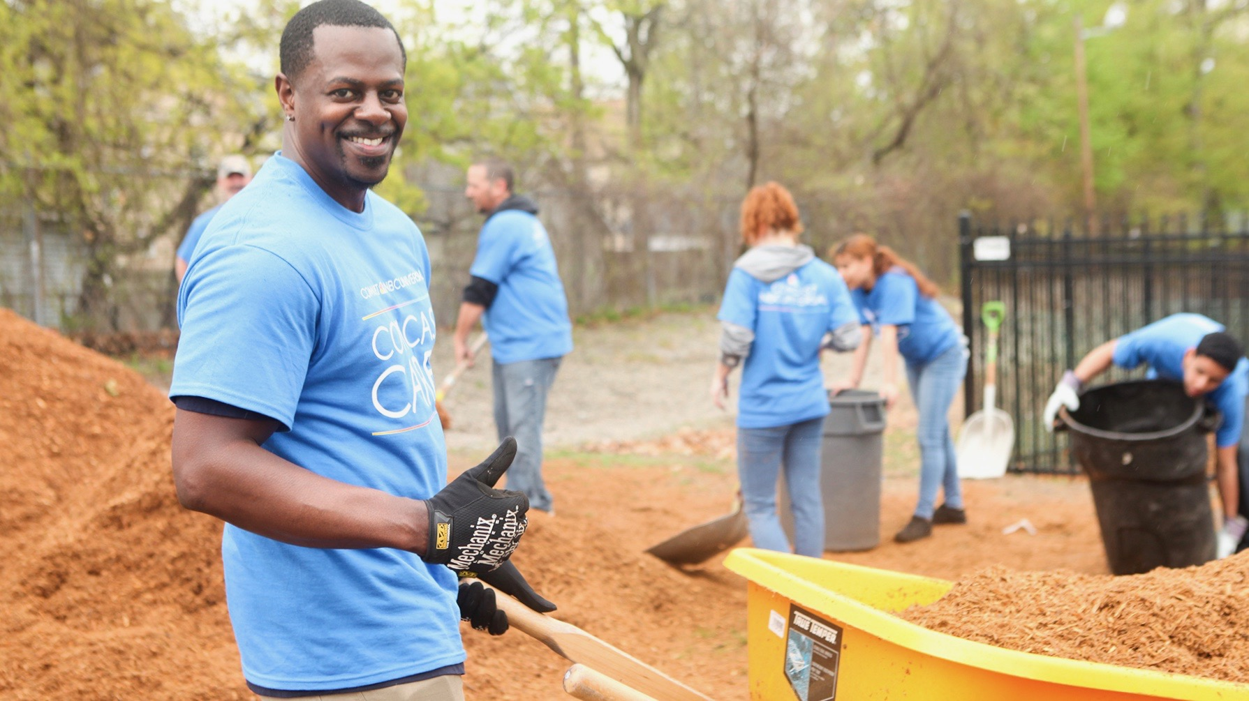 Comcast Cares Day volunteers carry mulch in wheelbarrows.