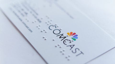 A Comcast business card covered in Braille.