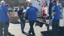 Comcast Cares Day volunteers unload a truck with electronics.