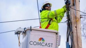 A Comcast technician repairs a cable